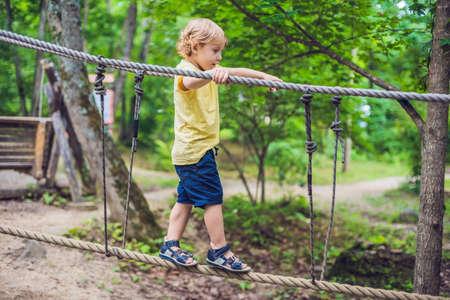 かわいい男の子の肖像画アドベンチャーパーク ロープでロープの橋の上を歩きます。