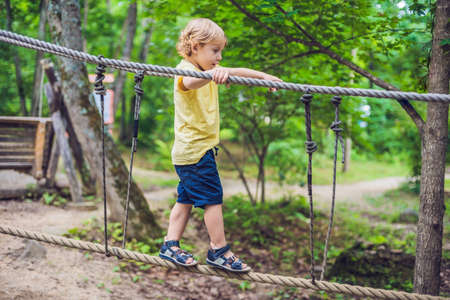 Portrait of cute little boy walks on a rope bridge in an adventure rope park.
