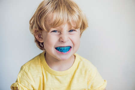 Three-year old boy shows myofunctional trainer to illuminate mouth breathing habit. Helps equalize the growing teeth and correct bite. Corrects the position of the tongue. Stock Photo
