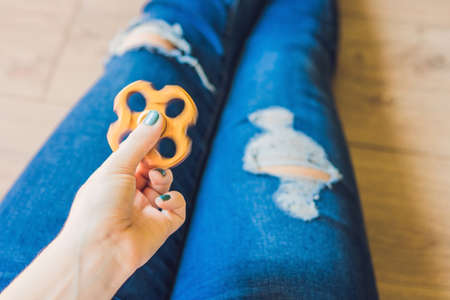 Girl teenager in holey jeans holds in hands and plays with spinner. Stock Photo