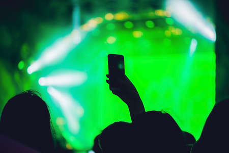People enjoying rock concert and taking photos with cell phone at music festival.