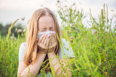 Young woman sneezes because of an allergy to ragweed. 스톡 콘텐츠