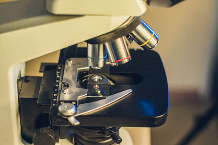 Optical microscope with four different objective lenses. Stock Photo
