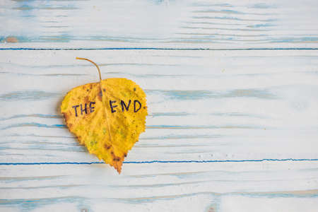 Yellow and green leaf with the inscription THE END on the old wooden background.