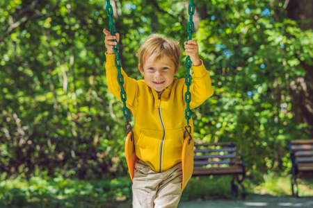 A boy in a yellow sweatshirt sits on a swing on a playground in autumn.