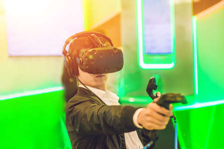 Young man playing video games virtual reality glasses. Cheerful man having fun with new trends technology - Gaming concept.