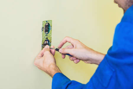 Electrician Installing Socket In New House. Electrician in the house Stock Photo