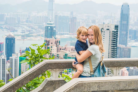 Mom and son travelers at the peak of Victoria against the backdrop of Hong Kong. Traveling with children concept.