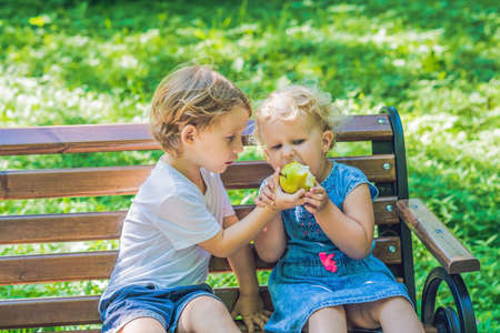 Toddlers boy and girl sitting on a bench by the sea and eat an apple.