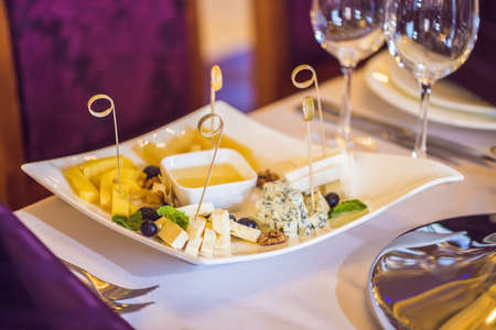 Honey and cheeses on a white plate, food. Stock Photo