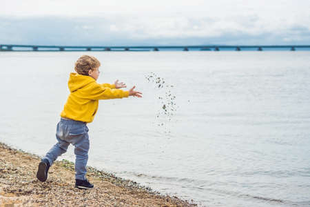 Young boy throwing stones in sea water.