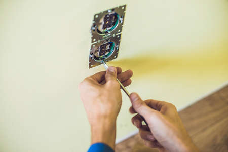 wall socket: Electrician Installing Socket In New House. Electrician in the house Stock Photo