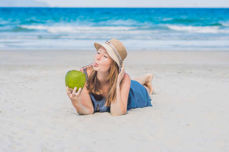 sexy asian woman: Attractive young woman drinking coconut water on the beach. Stock Photo