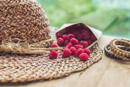 Summer holiday, vacation, relaxation concept. Raspberries, straw hat, on wooden background. Free text copy space. Summer vibes concept Stock Photo