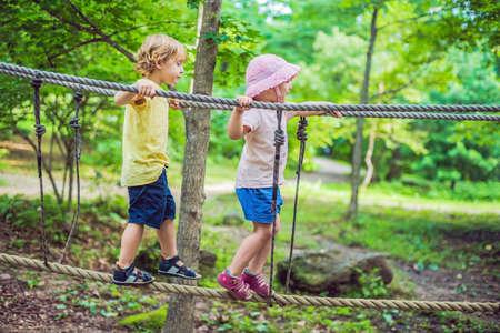 El retrato del pequeño niño lindo y la muchacha caminan en un puente de cuerda en un parque de la cuerda de la aventura. Foto de archivo