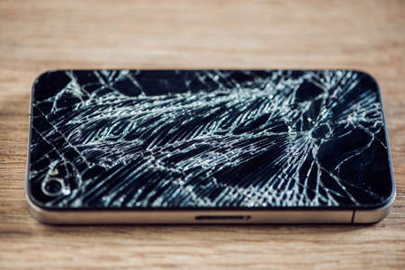 Smartphone display with broken glass on a wodden table. Stock Photo