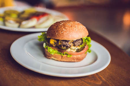 Hamburger with lettuce and tomato on white plate. junk food concept.