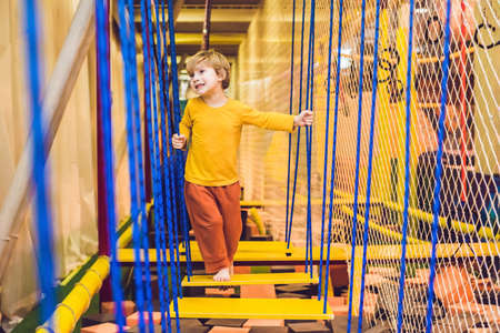 The boy passes the obstacle course in the sports club.