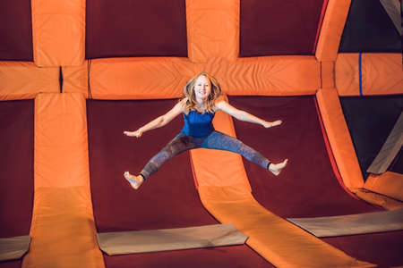 Young woman sportsman jumping on a trampoline in fitness park and doing exersice indoors.