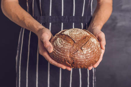 Baker man holding homemade rustic wheat bread in hands. Selective focus. 版權商用圖片