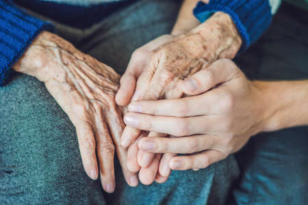 Hands of an old woman and a young man. Caring for the elderly. close up. Stock Photo