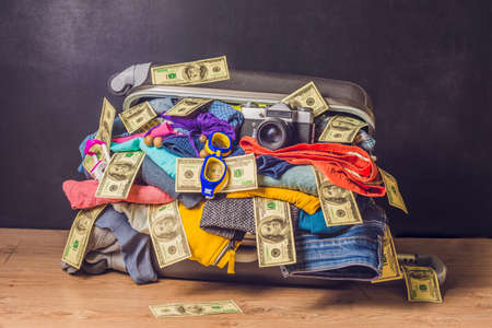 Packed suitcase with travel accessories and money on wooden background.