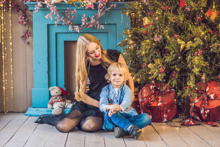 Portrait of happy mother and adorable boy celebrate Christmas. New Years holidays. Toddler with mom in the festively decorated room with Christmas tree and decorations. Stock Photo