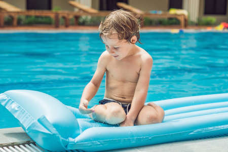 Smiling boy on blue inflatable mattress in the pool. Stock Photo
