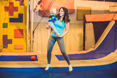 Mother And her son jumping on a trampoline in fitness park and doing exersice indoors. Stock Photo