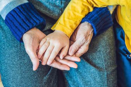 The hands of an elderly person and the hands of a child, the continuity of generations, the care of the elderly. Stock Photo