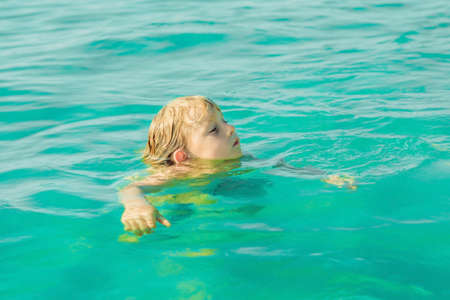 Boy swims in the blue tropical sea. hot summer. 스톡 콘텐츠