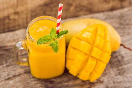 Healthy ripe Yellow Mango Smoothie, Mango fruit and mango cubes on the wooden table, concept healthy food.