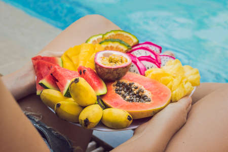 Young woman relaxing and eating fruit plate by the hotel pool. Exotic summer diet. Photo of legs with healthy food by the poolside, top view from above. Tropical beach lifestyle.
