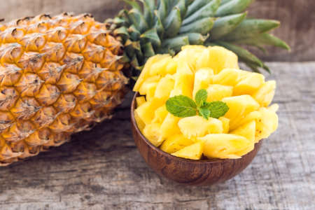 Pineapple slices and pineapple shelled Asian-style on the old wooden background. Tropical fruit concept.
