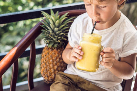 A boy drinks a pineapple smoothie on the terrace. 写真素材