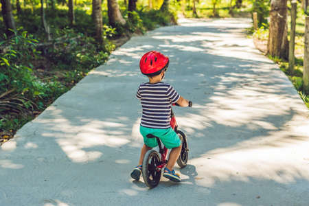 Little boy on a bicycle. Caught in motion, on a driveway motion blurred. Preschool child's first day on the bike. The joy of movement. Little athlete learns to keep balance while riding a bicycle. Stock fotó