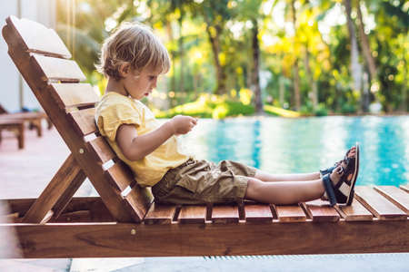 A cute little boy is using a smartphone lying on a deckchair by the pool. primary education, friendship, childhood, technology and people concept.