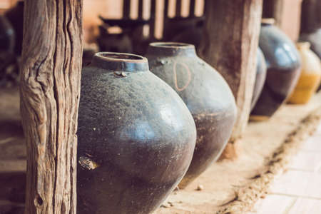 Ancient Vietnamese traditional pots overgrown with seashells.