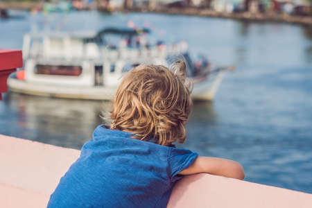 The boy admires the sea and colourful boats moored at Phu Quoc Vietnam. Boats such as these are iconic of the seaside port.