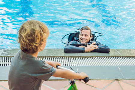 scuba diver in swimming pool and boy.