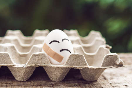 Broken egg with sticking plaster. Concept of brittleness and pain.