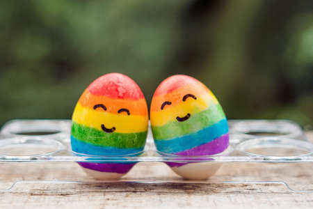 Two eggs are colored in the colors of the rainbow as a flag of gays and lesbians as well as Easter eggs. Homosexual concept. 스톡 콘텐츠
