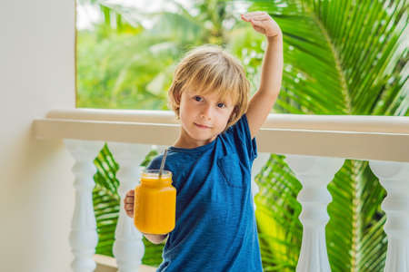 The boy holds mason jar of mango smoothies in his hand and shows how he grew up thanks to vitamins and food nutrition.