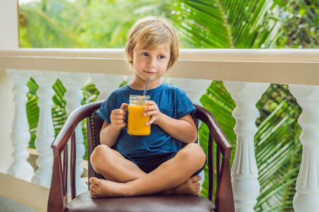 Boy drinking juicy smoothie from mango in glass mason jar with striped red straw on old wooden background. Healthy life concept, copy space. Stock Photo