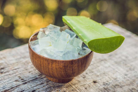 Aloe vera and aloe cubes in a wooden bowl. Aloe Vera gel almost use in food, medicine and beauty industry. Stock Photo