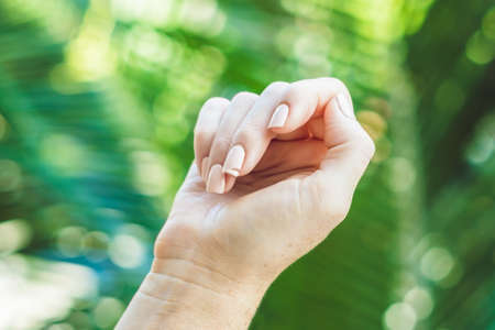 Broken nail on a womans hand with a manicure on a green background.
