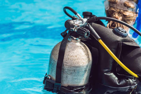 Grey scuba diving air oxygen tank on the back of a scuba diver.