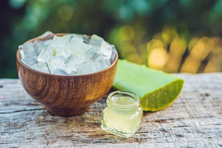 Slices of a aloe vera leaf and a bottle with transparent gel for medicinal purposes, skin treatment and cosmetics, close up.