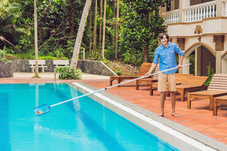 Cleaner of the swimming pool . Man in a blue shirt with cleaning equipment for swimming pools, sunny. Stock Photo