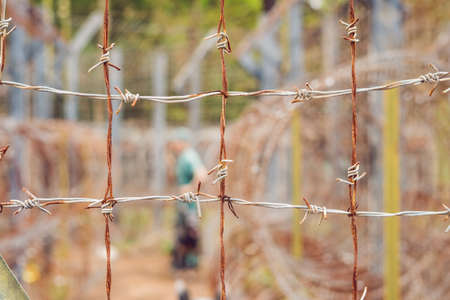 Barbed wire, a fence in prison and the silhouette of a prison guard on the background. Stock Photo